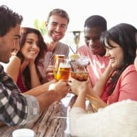 Group Of Friends Enjoying Drink At Outdoor Rooftop Bar, TapHunter